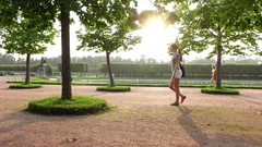 Young slender woman confidently go at formal garden, long slide shot Stock Footage