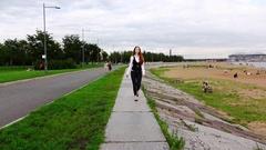 Office woman stroll in city park, walk along beach parapet, slow motion Stock Footage