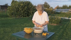 Elderly woman 80s cleans chanterelle mushrooms Stock Footage