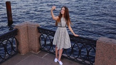 Cheerful young woman take selfie at old embankment, evening lighting Stock Footage