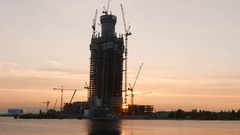 Tall tower frame against sunset sky, standalone skyscraper development site Stock Footage