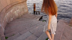 Happy brunette woman quickly run downstairs to river water Stock Footage