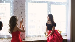 Two young women in red cocktail dress posing and photograps at smartphone on Stock Footage
