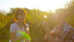 Girl and boy blowing a dandelion flower, dandelion seeds fly in sun, happy man Arkistovideo