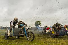 Caucasian racers on motorcycles with side cars spraying dirt Stock Photos