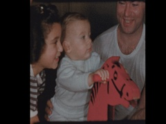 Family watches Little boy on 50's antique wooden rocking horse Stock Footage