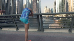 Young, sporty woman stretching leg on bridge in city, super slow motion 240fps Stock Footage