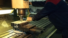 Worker adjust supply coolant on working drill on mill Stock Footage
