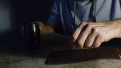 Man working on leather, making holes using hummer Stock Footage