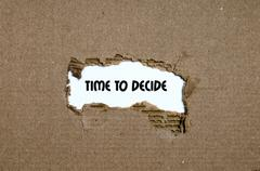The word time to decide appearing behind torn paper Stock Photos
