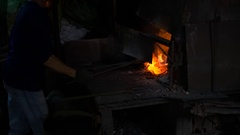 Blacksmith working in a smithery putting charcoal in a furnace oven Stock Footage