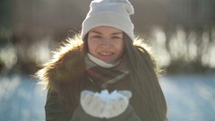 Beautiful Joyful Woman is Blowing away the Snow from Hands Having Fun Outdoors Stock Footage