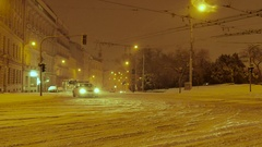 Snowplow and police car ride on a snow covered square, Central Europe, Night Stock Footage