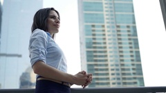 Young, pretty businesswoman relaxing on terrace and looking at skyscrapers Stock Footage