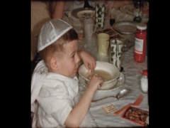 Young boy puts fingers in Matzo Ball soup served at Passover Seder Stock Footage