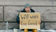 Homeless  beg for money on the street. Sign on cardboard - will work for food. Stock Footage
