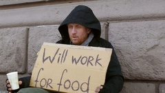 Homeless looking how much beg he got. Sign on cardboard - will work for food. Stock Footage