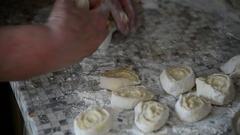 Grandma puts rolls of raw dough on table Stock Footage