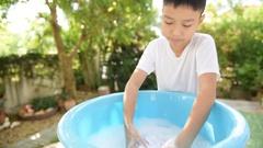 Boy washing cloth Stock Footage