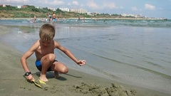 Little boy playing with sand, Constanta beach Romania, editorial Stock Footage