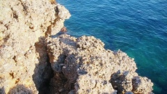 Rocky seashore with clear blue water Stock Footage