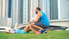 Young woman doing crunches in park with help of personal trainer Stock Footage