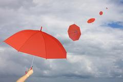 Red umbrella in hand and umbrella other blown by wind. Stock Photos