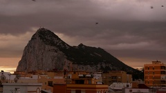The Rock of Gibraltar with dramatic sky and bird flock in flight above La Linea  Stock Footage