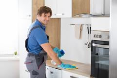 Worker In Overall Cleaning Countertop Stock Photos