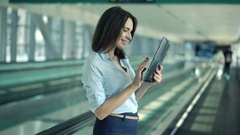 Young businesswoman using tablet computer while riding on escalator stairs Stock Footage