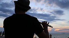 Man play flute at sunset on beach during full moon party. Koh Phangan, Thailand Stock Footage