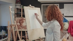 Female student working on a new painting in art class Stock Footage