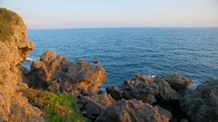Two guys traveler standing on the rocks the coast Stock Footage