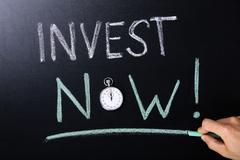 Invest Now Concept Written On Blackboard Stock Photos