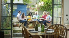 4K Happy 20s - 30s friends socializing with food & drinks outdoors on summer day Stock Footage