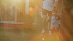 Artistic clip of year old toddler running outside. Lens flare hits camera Stock Footage