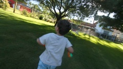 Happy child running outside Camera following kid while running in out Stock Footage