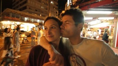 Happy young couple kissing candidly during nightlife. Stock Footage