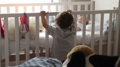 2 year old kid climbing baby brother's crib Stock Footage