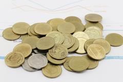 Pile gold coins on paper report of earnings. Stock Photos