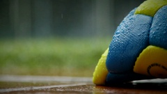 Rainy afternoon Artistic clip of soccer ball in the foreground and rain in the b Stock Footage