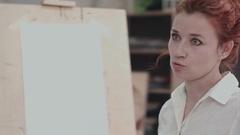 Young female painter near easel describing creative process Stock Footage