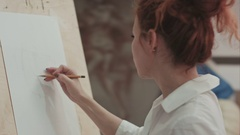 Young woman painter making sketches on blank canvas in artist workshop Stock Footage
