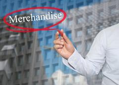 Hand of young businessman write the word Merchandise on skyscrapers backgroun Stock Photos
