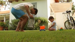 Baby toddler playing outside with toys Dad hanging with his son at home garden Stock Footage
