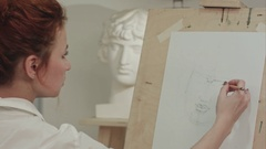 Concentrated woman artist painting plaster bust in art studio Stock Footage