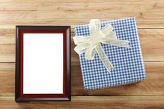 Blue gift box place near Brown wooden frame on the wood floor. Stock Photos