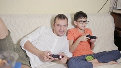 Father and son play video game inside their house on the couch Stock Footage