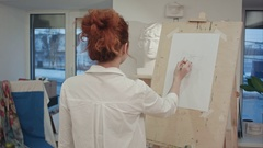 Female art student drawing plaster cast on easel Stock Footage