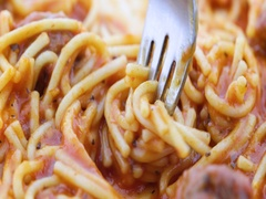 Close video of a spaghetti dinner on a plate with a fork trying to get a bite. Stock Footage